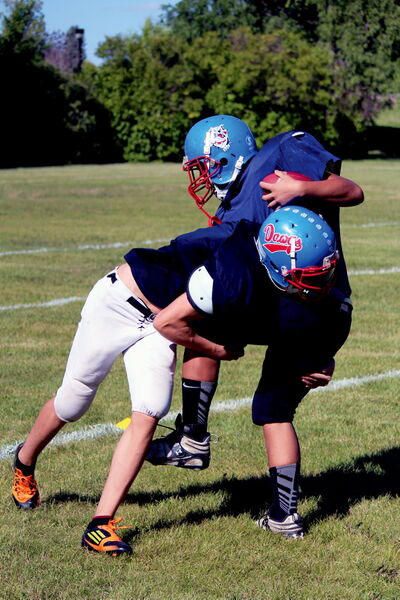 The Churchill Bulldogs high school football team runs through some tackling drills Aug.22.