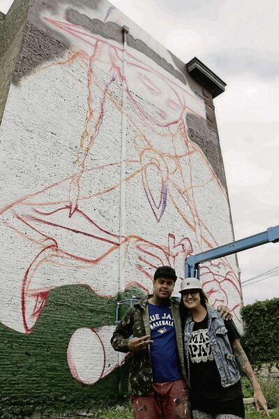 The Clandestinos Collective: Bruno Smoky (left) and Shalak Attack (right) stand in front of their painting, Mending, at the Winnipeg Centre Vineyard Church.