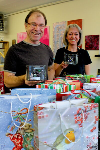 Brian McMillan and Heather Harris of Prairie Stained Glass gift wrap 40 handmade candle holders the business donated to Winnipeg Harvest last week.