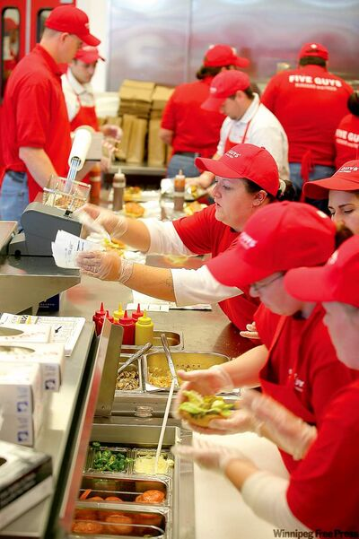 Workers at Five Guys Burger and Fries in Brandon prepare orders.