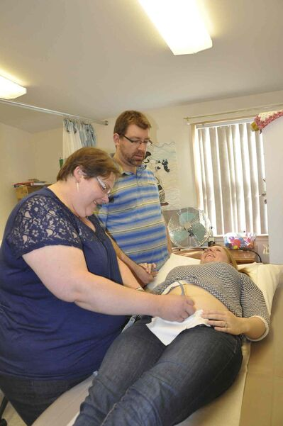 Midwife Amanda Tomkins (left) finds a fetal heartbeat for Allison Chidley and her husband Graham Wells to hear for the first time.