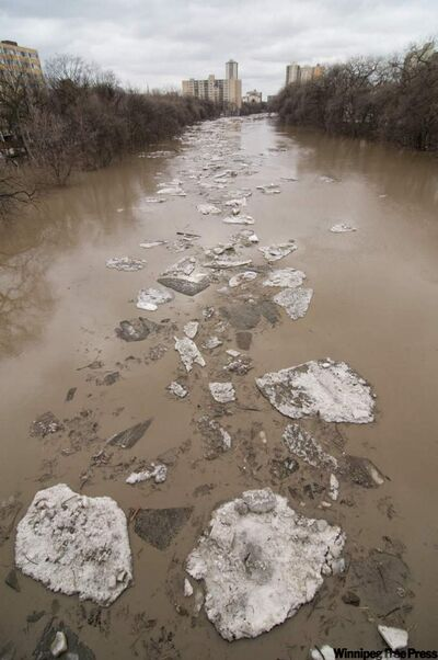 Ice flows down the Assiniboine River Sunday afternoon, as seen from the Donald Street Bridge in Winnipeg on Sunday.