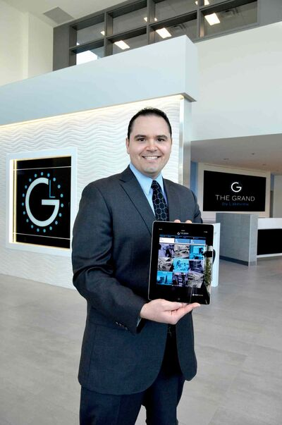 Neil Fishman, general manager at the Grand Winnipeg Airport Hotel by Lakeview, holds one of the hotel's iPads. Each guest room features an iPad for guests to use.