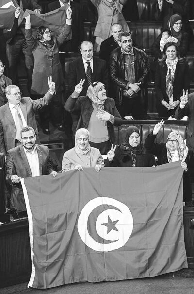 Members of the Tunisian National Constituent Assembly celebrate the adoption of a new constitution earlier this year. Of countries involved in the Arab Spring of 2011, only Tunisia has the makings of a real democracy.