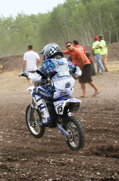 Travis Thauberger gets on the throttle of his Yamaha while his father Troy offers encouragement.