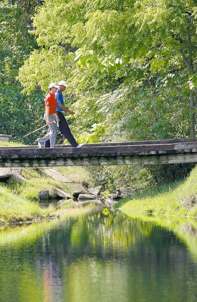 Charles Rex Arbogast / the associated pressTiger Woods (right) and Rory McIlroy cross the bridge on the sixth fairway during the first round of the BMW Championship.