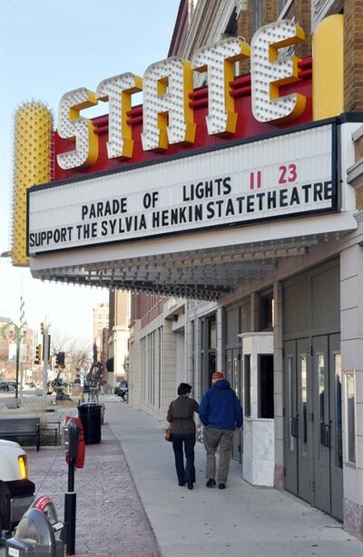 In this Nov. 17, 2012 photo a couple walks under the marquee of the historic downtown State Theatre in Sioux Falls, S.D. The circa-1926 movie house, closed since 1991, has been raising funds for its renovation and plans to begin showing films again in 2013. (AP Photo/Dirk Lammers)