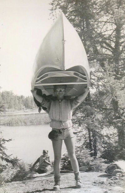 Carolyn Schram portages a canoe during the 1975 trip.