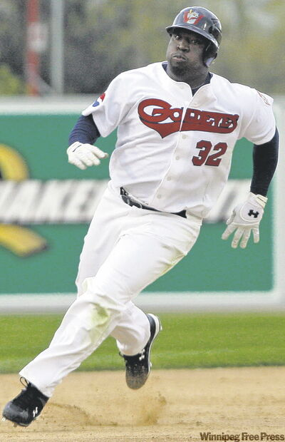 The Goldeyes' Dee Brown rounds third as coach Brent Metheny waves him on during Winnipeg's home opener Friday evening.