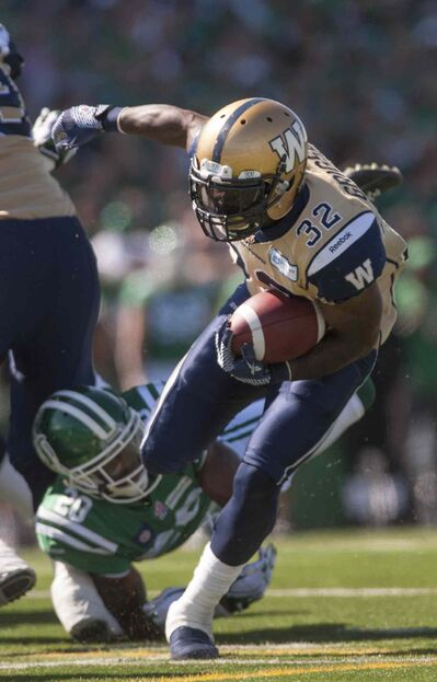 Bombers running back Nic Grigsby breaks a tackle from Roughriders' Terrell Maze on a day when all three Bomber touchdowns came on the run.