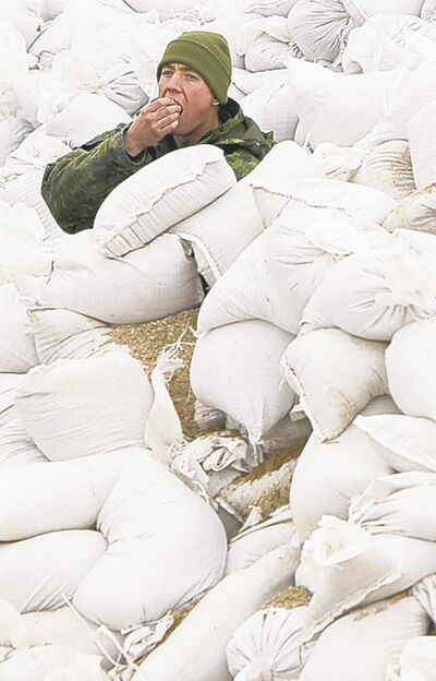 A soldier takes a break from  sandbagging duties in 2011.