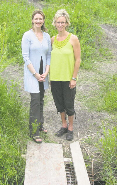 Royalwood resident Wendy Laurenco (right) and Southdale MLA Erin Selby at the site of what will be the Shorehill pedestrian path.