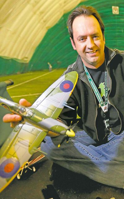 Randy Hepner of the Saints RC Flying Club holds a remotecontrolled Spitfire he flies twice a week at the Golf Dome.