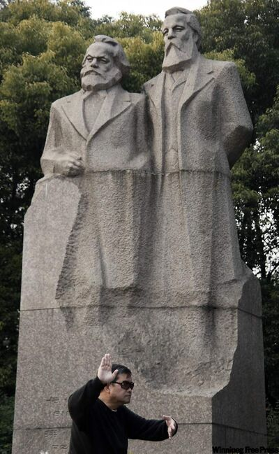A man practises tai-chi in front of a statue of Karl Marx, left, and Frederick Engels, right, the founders of communism, Thursday Dec. 23, 2010 in Shanghai, China.