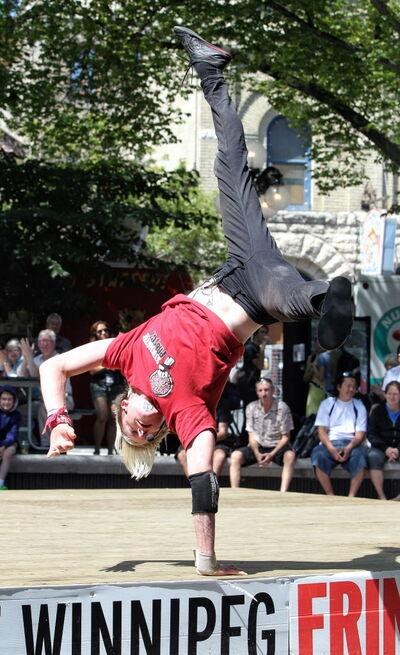 Mike Deal / Winnipeg Free Press Devin Shen of the Strength Project crosses the stage on his hands in Old Market Square during the final day of the fringe festival Sunday afternoon.