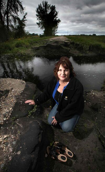 Municipal Counsellor Debbie McMechan in front of a washed out municipal road near Pierson.