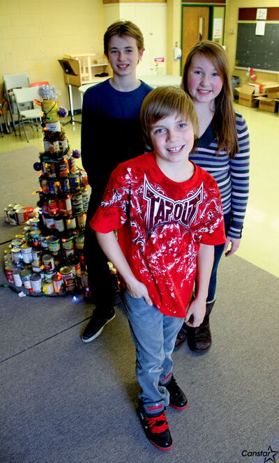 WMEMS students Anton Kriening (front), Stefan Kriening and Grace Bruinooge collected more than 500 items of food to donate to Siloam Mission.