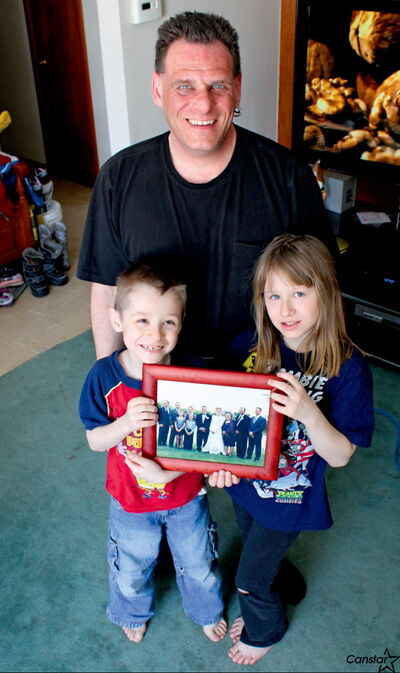 Warren Chapley (centre) with son Nolan and daughter  Morgan, and a picture of Cindy Chapley on her wedding day in 1999.