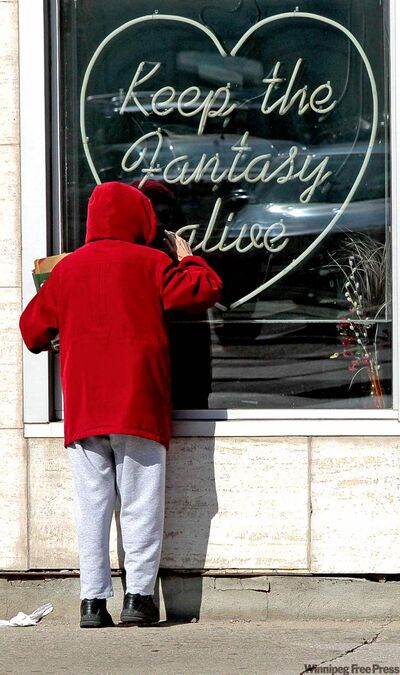 MIKE DEAL / WINNIPEG FREE PRESSA passerby looks into a shuttered Discreet Boutique Tuesday.