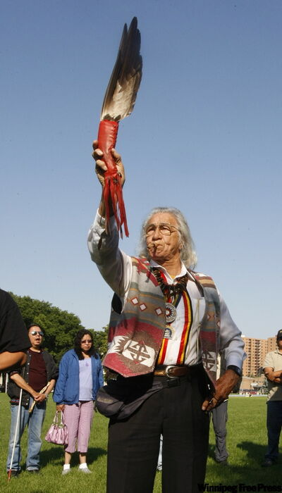 Emitt Eastman, an elder from the Dakota Sioux nation in South Dakota, blows a whistle and holds up an eagle feather in Memorial Park this morning to start prayers for runners taking part in the Run for Human Rights II. Runners will make a 2,000-mile journey from Winnipeg to Washington, DC to raise awareness about indigenous issues in Canada and the U.S.