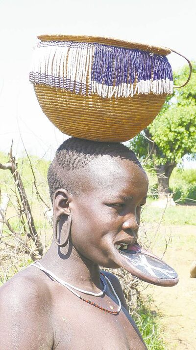Mursi women wearing huge clay plates in their bottom lips.