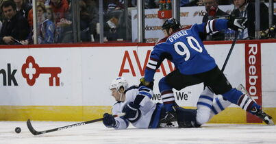 Winnipeg Jets defenceman Jacob Trouba, left, reaches out to clear puck out of the Jets' zone after being knocked down by Colorado Avalanche centre Ryan O'Reilly in the first period in Denver on Thursday.