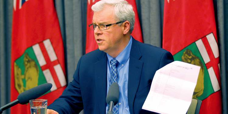 Phil Hossack / Winnipeg Free Press Premier Greg Selinger on Friday holds up a list of cabinet ministers and the free Jets tickets they received this past season.