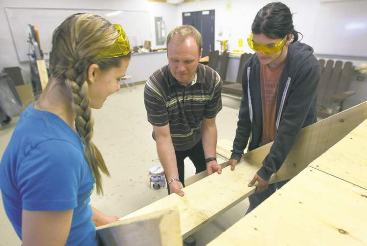 Rossburn Collegiate students Jenessa Cleland and Damian Beasley get help from principal Troy Luhowy (centre) at shops class.