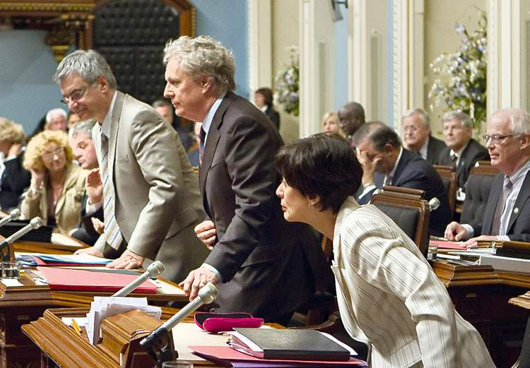 Clement Allard / The Canadian PressFrom left, Quebec Justice Minister Jean-Marc Fournier, Quebec Premier Jean Charest and Education  Minister Michelle Courchesne rise to vote on the emergency law Friday.