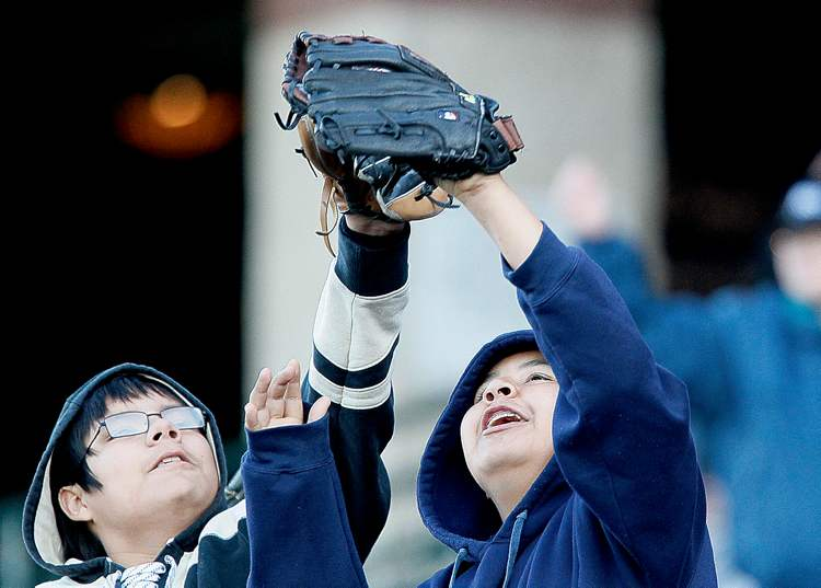 Two young fans go up for a fly ball at the Goldeyes home-opener against Amarillo Tuesday night at Shaw Park.