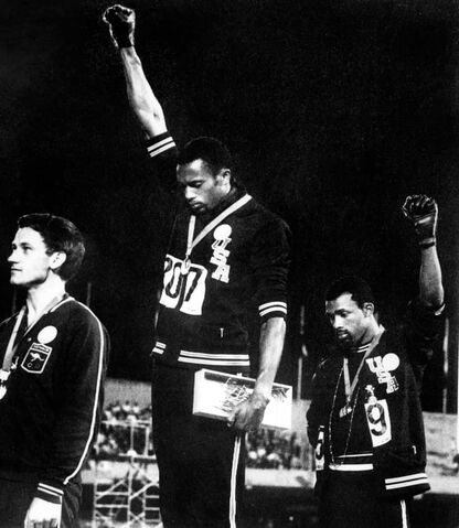 FRUS athletes Tommie Smith, center, and John Carlos, right, raise their gloved fists in the Black Power salute to express their opposition to racism in the USA during the US national anthem, after receiving their medals on Oct. 16, 1968 for first and third place in the men's 200m event at the Mexico Olympic Games. (EPU/AFP/Getty Images/TNS)