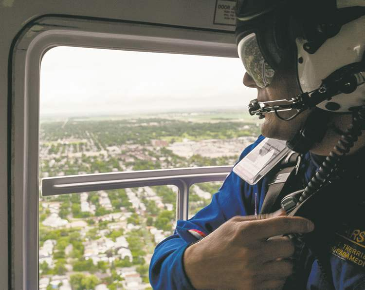 Flight paramedic Grant Therrien looks out the window of the STARS air ambulance Tuesday.