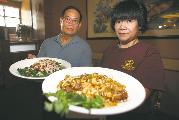 Phil Hossack / Winnipeg Free PressGeoffrey Young, owner and head chef at Kum Koon Gardens (left), holds pea tips with pork, while waitress Fa Young (no relation) poses with rice noodles and beef.