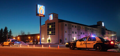 Members of the Brandon Police Service outside the Motel 6 on the Trans-Canada Highway after the killing last April.