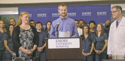 John Spink / MCTDr. Kent Brantly stands with his wife, Amber, while reading a statement at Emory University Hospital in Atlanta Thursday.