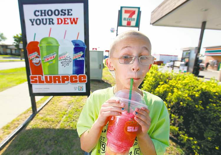Ruth Bonneville / Winnipeg Free Press  Aidan Pratt, 9, enjoys his favourite Slurpee flavour -- cream soda and lime -- Thursday while helping his mom Kristina Pratt pick up Slurpees for the family.