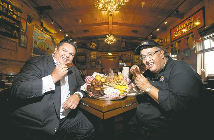 Allan McLeod, left, and 'Famous'  Dave Anderson dig in at the restaurant chain's new Reenders Square location.