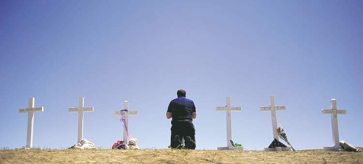 Aaron Ontiveroz / The Associated Press Travis Hirko kneels in front of the cross for friend Alex Sullivan at a memorial in Aurora, Colo., Sunday. Sullivan was killed during Friday's shooting rampage.