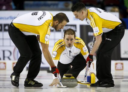 Manitoba skip Reid Carruthers looks on as second Derek Samagalski, left, and lead Colin Hodgson sweep his shot during action at the Brier in Calgary.