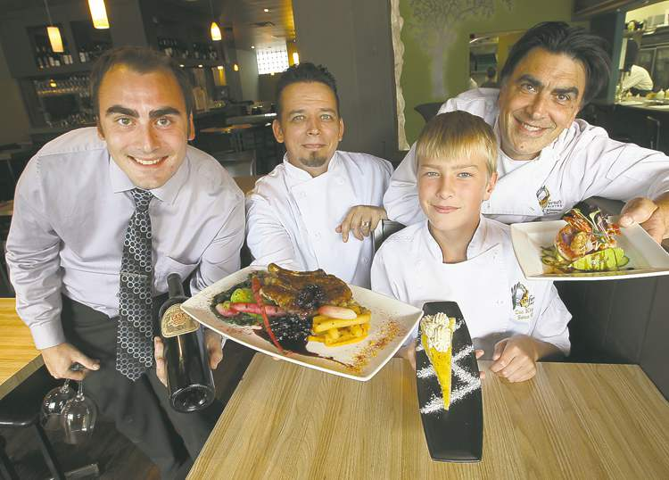 From left: co-owner Chris Kirouac, head chef Chris Chornopyski with pork chop, Zach Kirouac with torte, and co-owner Fern Kirouac with sake prawns.