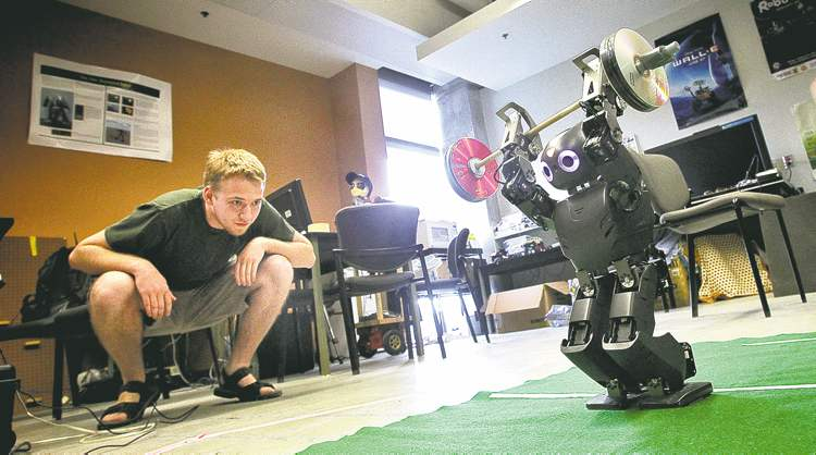 Mike Deal / Winnipeg Free PressSimon Barber-Dueck watches as Jimmy the robot practices his weightlifting moves in preparation for the annual robot Olympics in Bristol.
