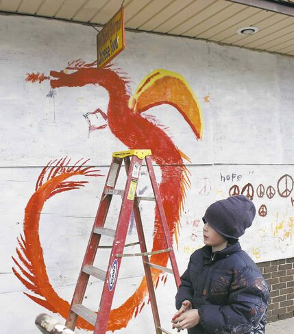 Several children aided by their parents put the finishing touches on a dragon painted on plywood in downtown Ferguson, Mo., Thursday, Nov. 27, 2014. The unpainted plywood was placed on a Chinese restaurant, and on other buildings in Ferguson to prevent vandals from causing damage after a grand jury chose not to indict a white Ferguson police officer in the shooting death of an unarmed black man. (AP Photo/Skip Foreman)