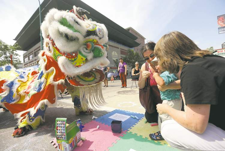 Members of The Lion Dance, performed by the Ching Wu Athletic Association, stop to meet Daphne Young, her son Franco Young, 19 months, and Heather Millar, during the Chinatown Street Festival Saturday.