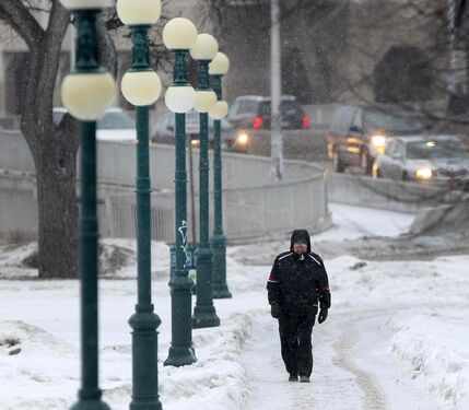 A pedestrian walks down a sidewalk at the Manitoba Legislature during a grey, dark Monday morning today in Winnipeg.