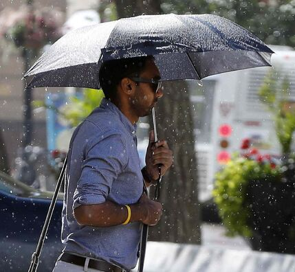 A short downpour ending with a sun shower hit the city just after 3 p.m. causing pedestrians downtown to pop their umbrellas.