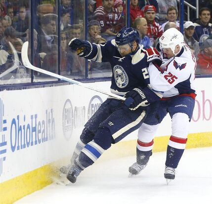 Columbus Blue Jackets' James Wisniewski (21) is jammed into the boards by Washington Capitals' Jason Chimera (25) in the first period of an NHL hockey game, Thursday, Dec. 18, 2014, in Columbus, Ohio. (AP Photo/Mike Munden)