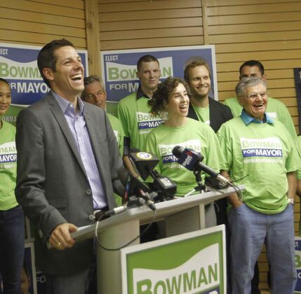 Mayoral candidate Brian Bowman and supporters respond to a reporter's question at a briefing in his campaign office Friday morning.