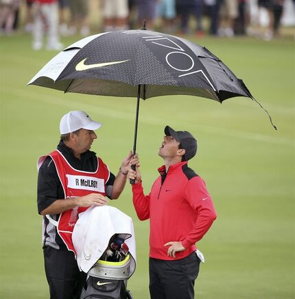 Northern Ireland's Rory McIlroy, right, and his caddy J.P. Fitzgerald shelter under an umbrella during the first round of the Australian Open golf championship in Sydney, Australia Thursday, Nov. 27, 2014. McIlroy shot a 2-under 69. (AP Photo/Rick Rycroft)