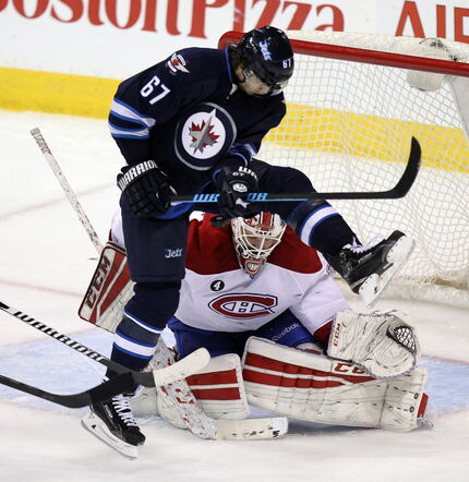 Montreal Canadien netminder #35 Dustin Tokarski looks for the puck between Michael Frolik's legs as the Winnipeg Jet screens the play in the third period at the MTS Center Thursday night.