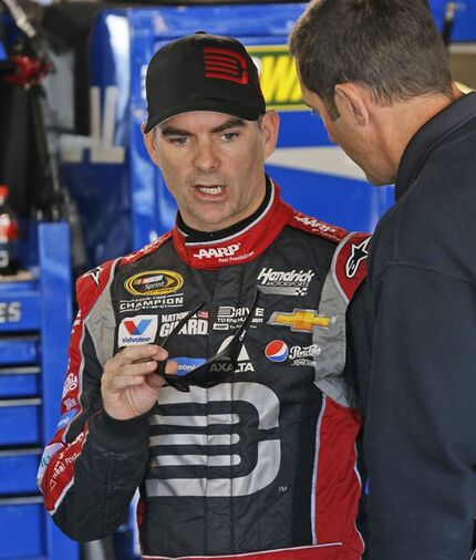 Jeff Gordon talks to his crew in the garage as he waits for practice to begin for Sunday's Sprint Cup Series auto race at Martinsville Speedway in Martinsville, Va., Saturday, Oct. 25, 2014. (AP Photo/Steve Helber)
